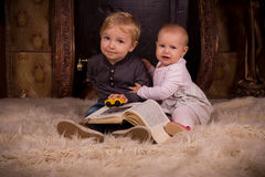 Children on a fluffy carpet with book Stock Photography