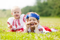 Children in  folk clothes on grass Stock Image