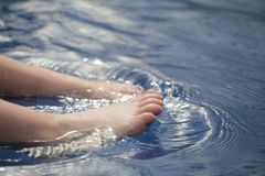 Children foot swimming pool background. Day light stock photography