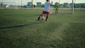 Children football players are training scoring goal. On open stadium stock video