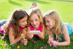 Children friend girls playing internet with smartphone. Children friend girls group playing internet with mobile smartphone on grass Royalty Free Stock Photos