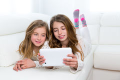 Children friends kid girls playing together with tablet pc. Children sister friends kid girls playing together with tablet pc lying on white sofa Stock Photo