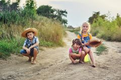 Children friends on a walk in the countryside barefoot . Children on a walk in the countryside barefoot . Happy kids with dirty feet . Dusty village road stock photography
