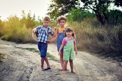 Children friends on a walk in the countryside barefoot . Children on a walk in the countryside barefoot . Happy kids with dirty feet . Dusty village road stock image