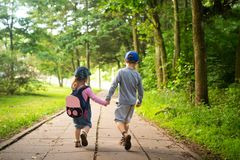 Children friends walking in summer park and hold hands. Child friendship stock photos
