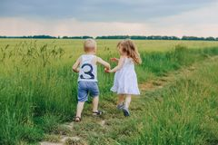 Children friendship love hands escape nature spring. Little children boy and girl running along the path the field hold on to the hand on nature Royalty Free Stock Photo