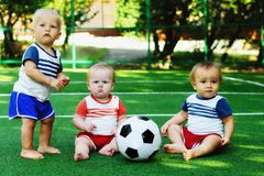 Children friendship: three little kids at sports ground with soccer ball. Tiny football team learning to play and to walk stock image