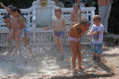 Children frolic in the fountain jets. Peterhof, Russia Royalty Free Stock Photography
