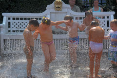 Children frolic in the fountain jets Stock Image