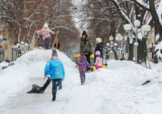 Children frolic on the snowy hill Royalty Free Stock Photography