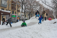 Children frolic on the snowy hill Royalty Free Stock Photo