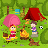 Children fry sausages on the bonfire in the summer camp Royalty Free Stock Image