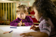 Children and fun, preschoolers drawing at school. Children having fun at school, two young girls drawing in kindergarten with sad child contemplating her drawing Stock Photography