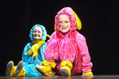 Children in funny colored overalls aliens  dancing on stage Stock Photography