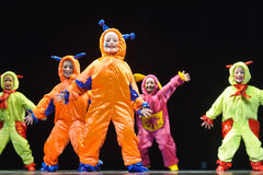 Children in funny colored overalls aliens  dancing on stage Royalty Free Stock Photos