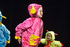 Children in funny colored overalls aliens  dancing on stage Stock Photos