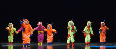 Children in funny colored overalls aliens  dancing on stage Stock Image