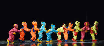 Children in funny colored overalls aliens dancing on stage stock images