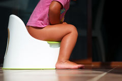 Children& x27; gambe di s che pendono giù da un vaso da notte Immagine Stock