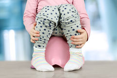 Children& x27; gambe di s che pendono giù da un vaso da notte su un fondo blu Immagini Stock Libere da Diritti