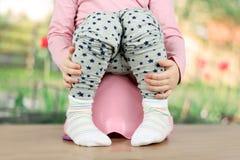 Children& x27; gambe di s che pendono giù da un vaso da notte su un fondo verde Fotografie Stock