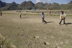 Children games. In the drained paddy children play a kind of hockey. The game is to return the roller Using a stick. The roller is a slice cut from a worn thong Stock Image