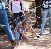 Children games. Girl goes through the tangled rope stock photography