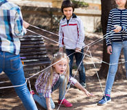 Children games. Girl goes through the tangled rope Royalty Free Stock Images
