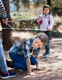 Children games. Girl goes through the tangled rope Stock Photos