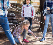 Children games. Girl goes through the tangled rope Royalty Free Stock Photos