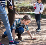 Children games. Girl goes through the tangled rope Stock Images