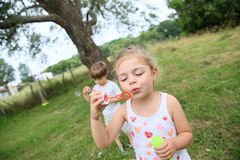 Children in the garden blowing soap bubbles Royalty Free Stock Image