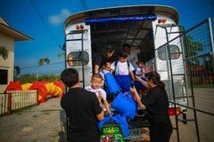 Children Getting off School Bus by teacher. Phrae Thailand - May 8, 2017: Children Getting off School Bus by teacher Royalty Free Stock Photos