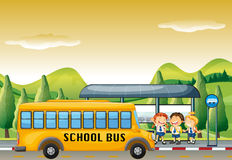 Children getting on school bus at bus stop Stock Image