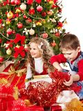 Children with gift box near Christmas tree. Royalty Free Stock Photography