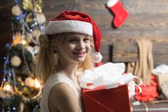 Children gift. Cute little girl near Christmas tree. Portrait kid with gift on wooden background. Kid enjoy the holiday royalty free stock images