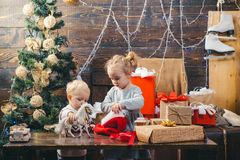 Children gift. Winter evening at home. Portrait of happy child looking at decorative toy ball by Christmas tree. Babies royalty free stock image