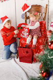 Children with gifts beside Christmas tree Royalty Free Stock Photography