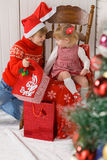 Children with gifts beside Christmas tree Royalty Free Stock Images