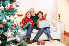 Children with gifts and grandfather at christmas Stock Photos