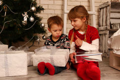 Children with gifts near a Christmas tree Stock Image
