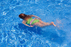 Children gilr swimming underwater in blue pool Royalty Free Stock Photography