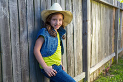 Children girl as kid cowgirl posing on wooden fence Royalty Free Stock Photo