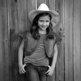 Children girl as kid cowgirl posing on wooden fence Stock Photos