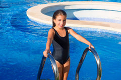 Children girl on the blue pool stairs black swimsuit Stock Photo