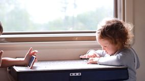 Children girl and boy play in the game with smartphone in train. Child playing game on the mobile phone in the road. The concept of travel and trip stock footage