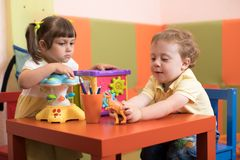 Children girl and boy play in kids daycare center stock image