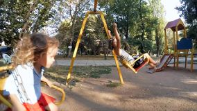 Children Girl and boy on a swing ride . Two cute children swinging on playground stock footage