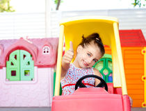 Children girl driving a toy car with ok gesture Stock Images