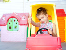 Children girl driving a toy car with ok gesture Stock Photography